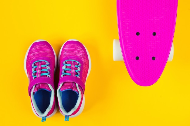 Pink skateboard and sneakers on yellow background flat lay
