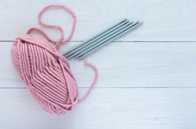 흰색 나무 배경에 분리된 뜨개질 바늘이 있는 분홍색 타래, 뜨개질 장갑 또는 양말 5개 바늘