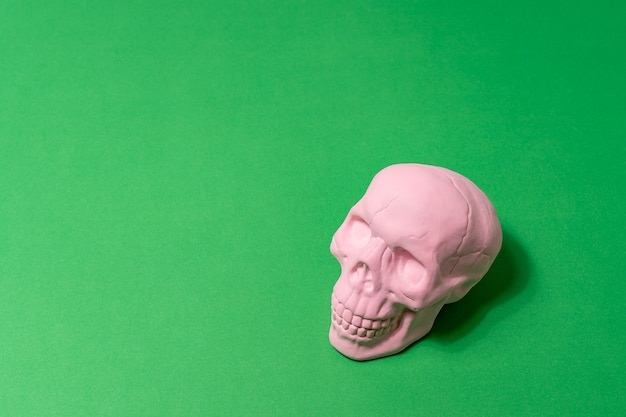 緑の背景にピンクの頭蓋骨