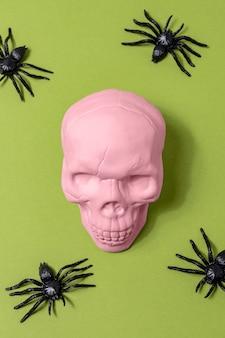 明るい背景にクモとピンクの頭蓋骨