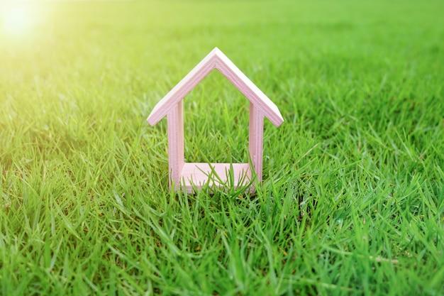 Розовый домик в саду с зеленой травой или в парке солнечным утром