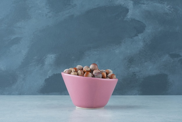A pink small plate full of nuts on marble background. high quality photo