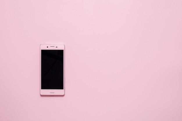 Розовый смартфон или мобильный телефон на розовом фоне с копией пространства. плоская планировка. вид сверху. фото высокого качества