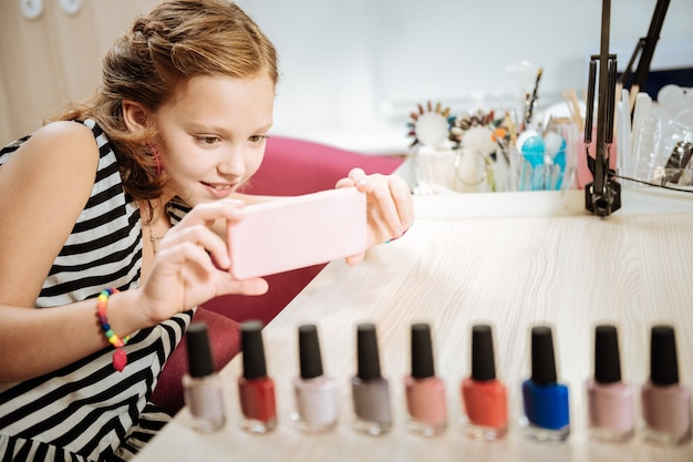Pink smartphone. teenager wearing striped dress holding pink smartphone making photo of nail polish