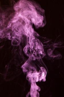 黒の背景にピンクの煙オーバーレイテクスチャの動き