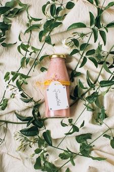 葉の横にある瓶の中のピンクのスムージー