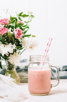 Pink smoothie next to vase with roses