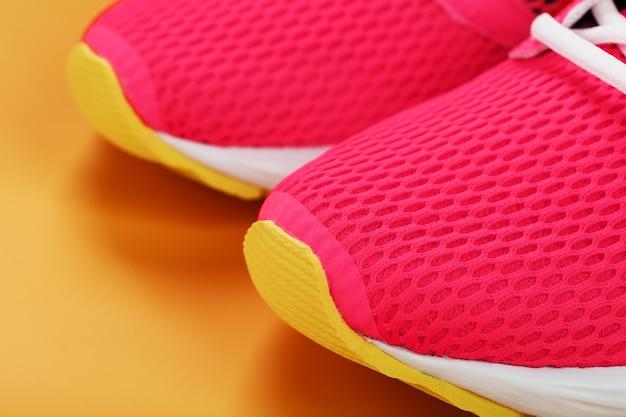 여유 공간이있는 노란색 배경에 핑크 스니커즈. 평면도, 최소한의 개념