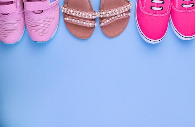 青色の背景に女の子のためのピンクのスニーカー、ゴム長靴、サンダル。別の靴。