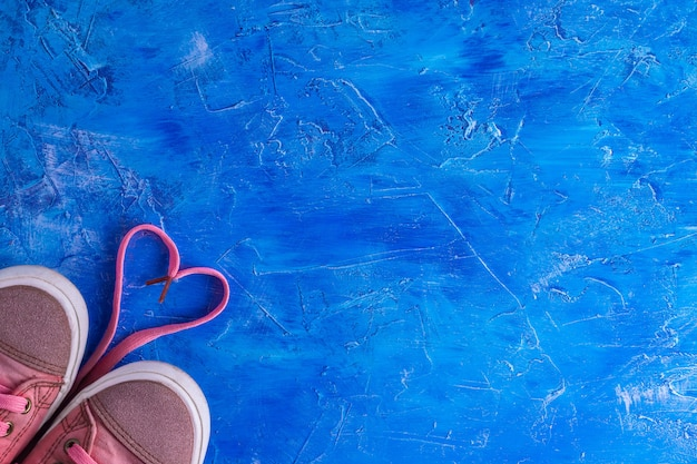 Pink sneakers with laces a heart on a blue background