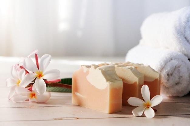 분홍색 비누를 테이블 위에 놓고 꽃과 수건을 옆에 놓습니다.
