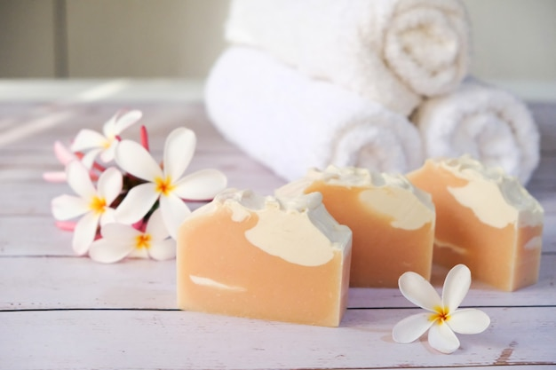 На стол кладут розовое мыло, на бок кладут цветы и полотенца.