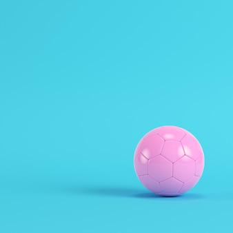 Pink soccer ball on bright blue background