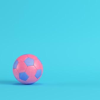 Розовый футбольный мяч на ярко-синем фоне