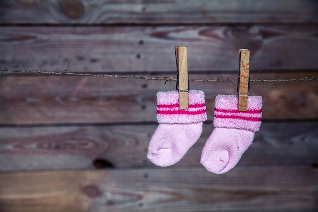 ピンクの靴下は洗濯はさみの木製の背景に掛ける