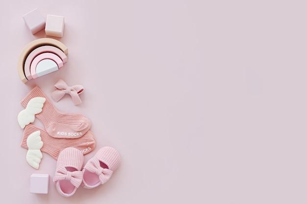 분홍색 양말, 신발, 장난감. 파스텔 배경의 소녀를 위한 아기 물건과 액세서리 세트. 베이비 샤워 개념입니다. 패션 신생아입니다. 평평한 평지, 평면도