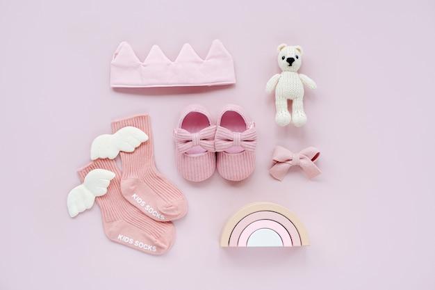 분홍색 양말, 신발, 면 왕관 및 장난감 곰. 파스텔 배경의 소녀를 위한 아기 물건과 액세서리 세트. 베이비 샤워 개념입니다. 패션 신생아입니다. 평평한 평지, 평면도