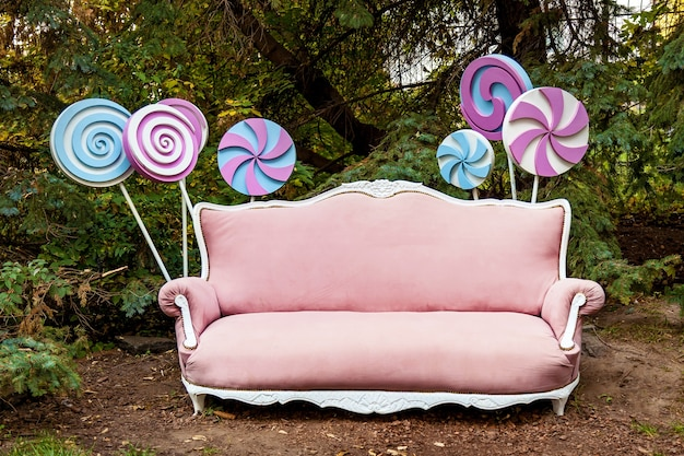 Pink sofa and large round candy. festive photo area on the street with furniture, free space. holiday concept