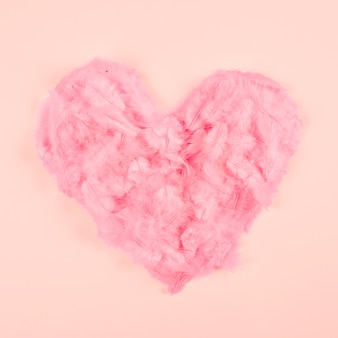 Pink soft feather heart shape on peach colored background