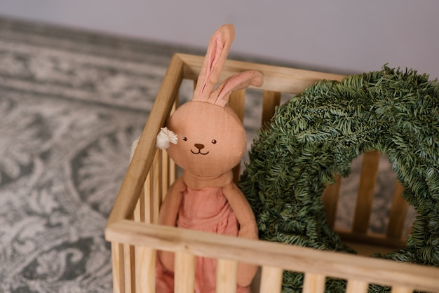 나무 상자에 부드러운 장난감 토끼와 크리스마스 화 환 핑크