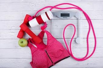 Pink sport bra, red bars, thermomug, green apple, jump rope lie