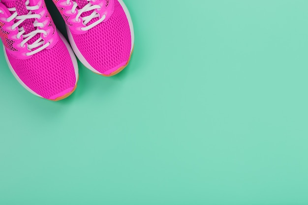 空きスペースのある青い背景で走るためのピンクのスポーツスニーカー。上面図、ミニマルなコンセプト
