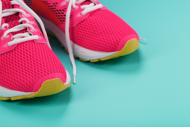 Pink sports sneakers for running on a blue with free space Premium Photo