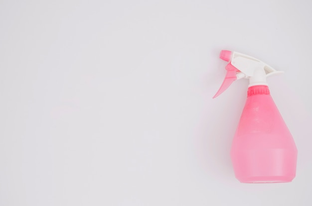 Pink spray bottle on white background