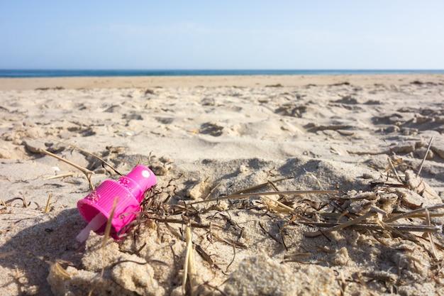 Розовая шапочка-распылитель на пляжном песке. пластиковое загрязнение концепции океанов.
