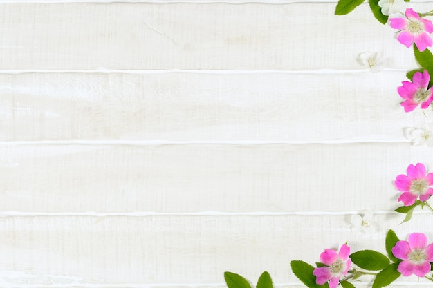 Pink spring flowers on white wooden table floral background