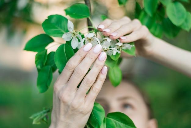 짧은 손톱에 분홍색 봄 매니큐어 젤 폴란드어. 여자가 꽃이 만발한 사과 나무를 들고입니다.