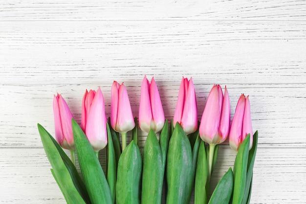 Розовые весенние тюльпаны на фоне белых досок. место для текста.