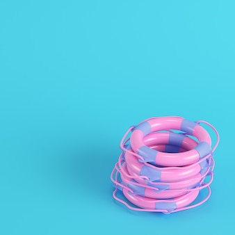 Pink stack life buoys on bright blue background