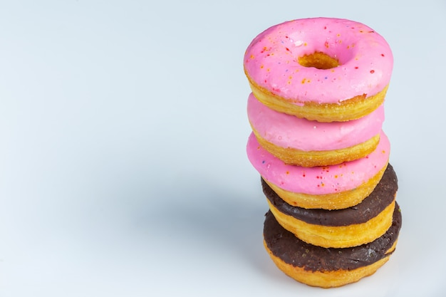 Pink stacked chocolate glaze doughnut  on color wall.