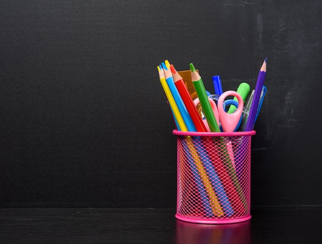 Pink stationery glass with multi-colored wooden pencils and pens, black chalkboard background, copy space