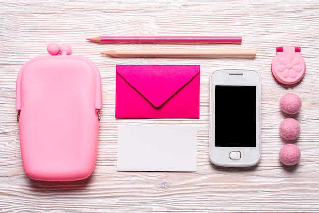 Pink stationery tools for girl, coin purse, envelope for business card, smart phone, on wooden background