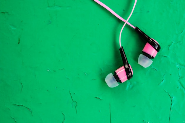 Pink stereo earphones on wooden green background