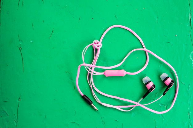 Pink stereo earphones on wooden green