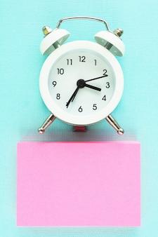 ピンクのステッカーブロックと青い紙の背景に白い目覚まし時計。テキスト用のスペース。