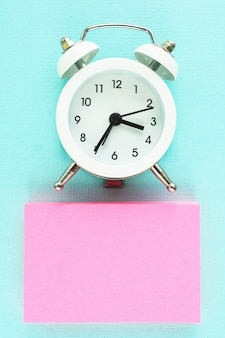 Pink sticker block and white alarm clock on a blue paper background. space for text.