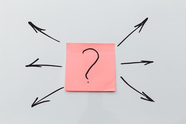 물음표와 많은 화살표가있는 분홍색 스티커. 방향 선택의 개념.
