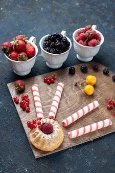 ピンクの粘着性のあるキャンディーとベリーフルーツケーキのダークフルーツベリーキャンディースイートグッディボンボン