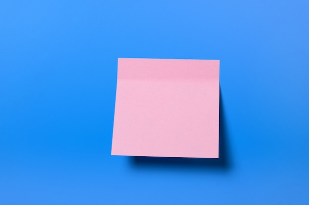 Pink sticky sticker for informational reminder, on a blue background