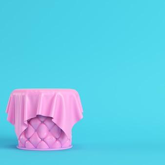 パステルカラーの明るい青色の背景に生地で覆われたピンクのステッチ台座