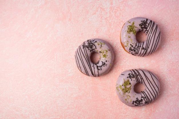 Розовые пончики клубники, изолированные на розовом фоне.