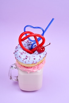 Pink strawberry freakshake with marshmallow and sweets.