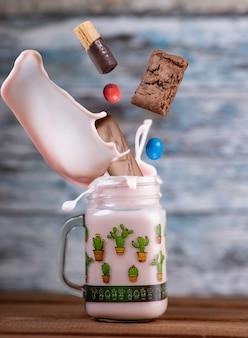 落ちる空気中のお菓子とピンクのイチゴのフリークシェイク