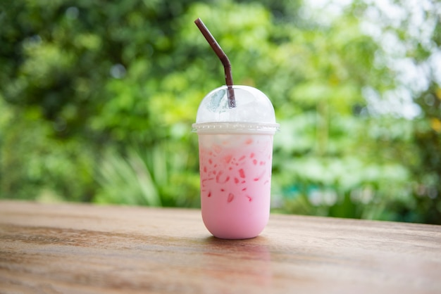 Pink strawberry milk pink ice drink in plastic cup juice for summer and straw on wooden table with nature