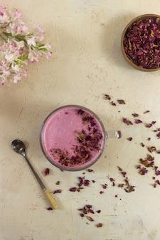 テーブルの上のピンクのイチゴのミルクセーキ