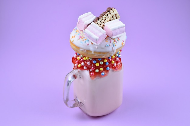 Pink strawberry milkshake with marshmallow and sweets
